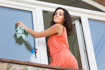 Young woman washing plastic windows in house