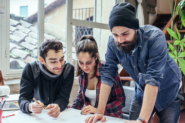 Teamwork. Three young architects working on a project