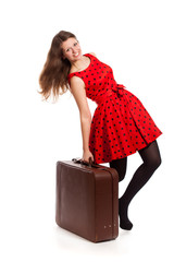 A smiling woman is holding a suitcase