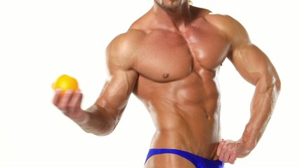 Shaped and healthy body man holding a fresh orange, shaped