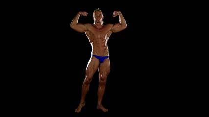 Bodybuilder posing over black background