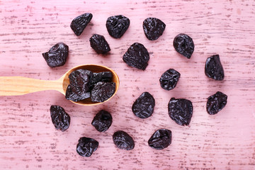 Spoon of prunes on color wooden background