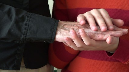 Child petting her grandmother old wrinkled hands