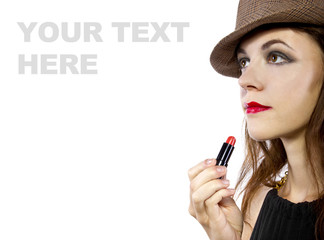 young female with hat applying red lipstick on white background
