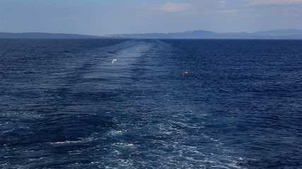 Seagulls over track from the ship in Aegean Sea.