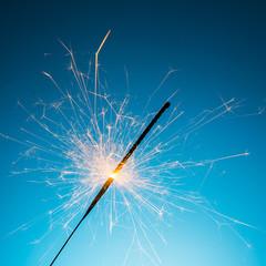 burned sparkler on blue
