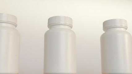 Close up of row of white bottles on conveyor belt