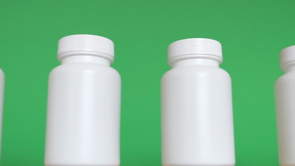 Row of white bottles against green background isolated
