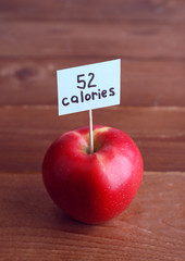 Red apple with calories count label on wooden table background