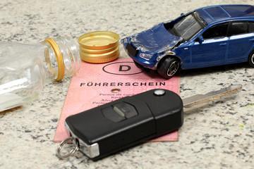 Alkoholflasche liegt auf Führerschein, Autowrak