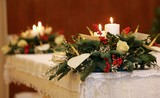 two bunches of flowers and two lit candles on the altar