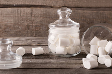 white marshmallows spilling from a jar on wooden background