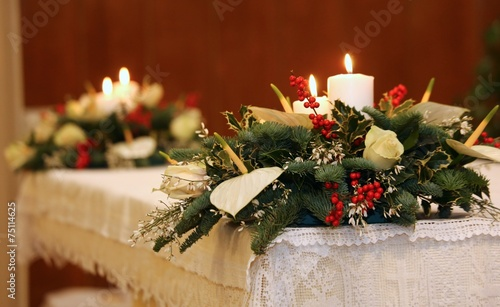 Foto op Canvas Bedehuis two bunches of flowers and two lit candles on the altar