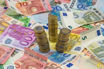 Münzenstapel auf Euro Banknoten