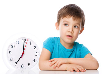 Boy is holding big clock