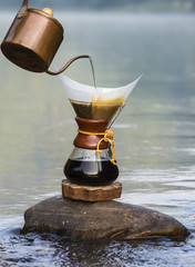 hand drip coffee  on the rocks at the river