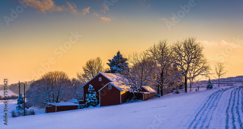 Winter view of a barn on a snow covered farm field at sunset, in