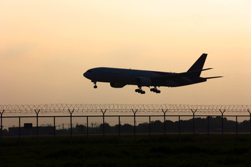 Silhouette airplane take off  the runway on the morning sky.