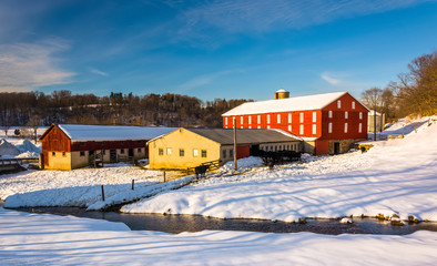Winter view of a red barn and a stream in Seven Valleys, Pennsyl