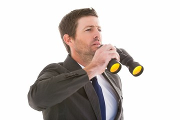 Focused handsome businessman holding binoculars
