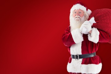 Composite image of santa carries his red bag and smiles