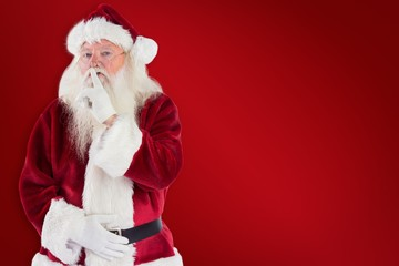 Composite image of santa asking for quiet to camera