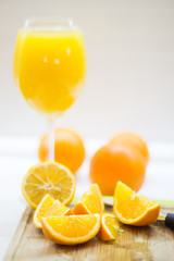 Fresh cutted orange and juice on wooden plank