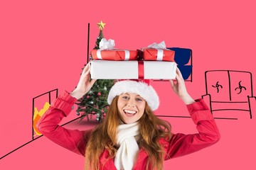 Composite image of festive redhead holding pile of gifts