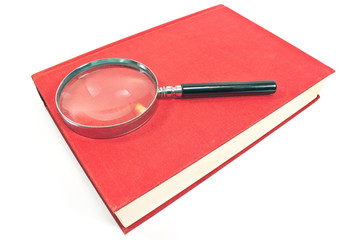 Antique magnifying glass on red book isolated on white