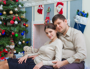 married couple on the background of the Christmas tree