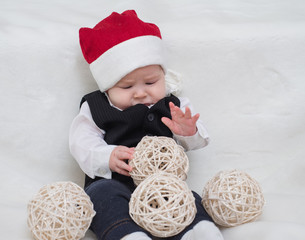 Baby in Santa Claus hat lying on the carpet