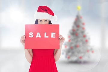 Composite image of brunette in red dress holding sale sign