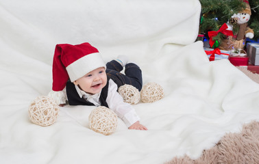 Baby in Santa Claus hat lying on the carpet.