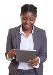Lachende Geschäftsfrau aus Afrika arbeitet am Tablet