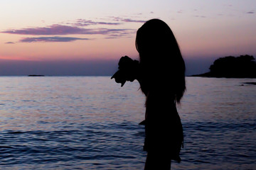 silhouette of young beautiful woman on the beach