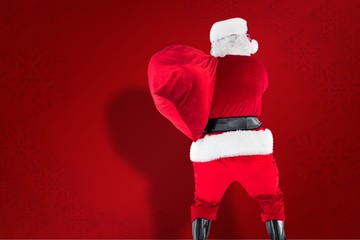 Composite image of rear view of santa holding a sack