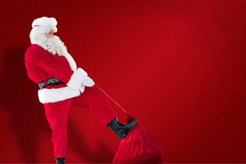 Composite image of santa claus clothing his sack