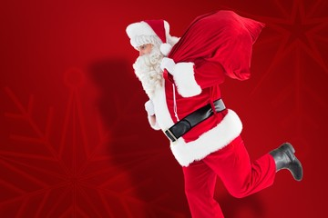 Composite image of santa claus walking with a sack
