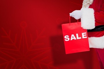 Composite image of santa claus holding sale bag