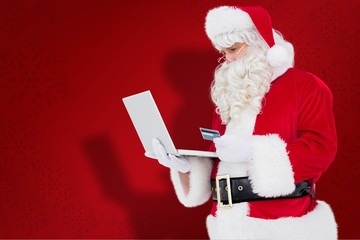 Composite image of santa claus shopping online with laptop