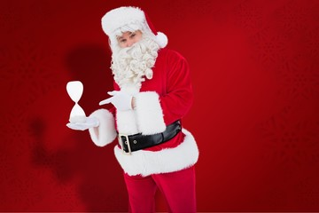 Composite image of smiling santa claus holding hourglass