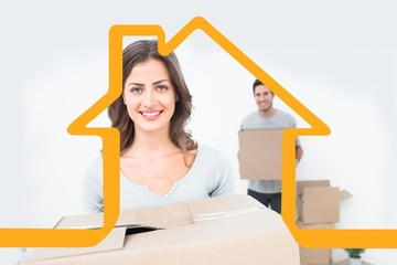 Composite image of pretty woman holding boxes in her new house
