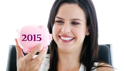 Composite image of laughing businesswoman holding a piggybank