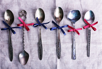 Metal spoons on white fabric background