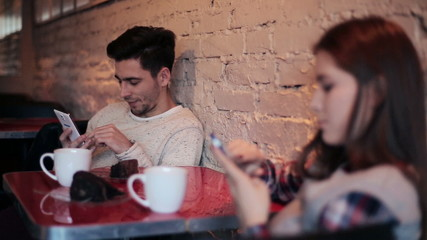 couple using and staring at smartphone in cafe