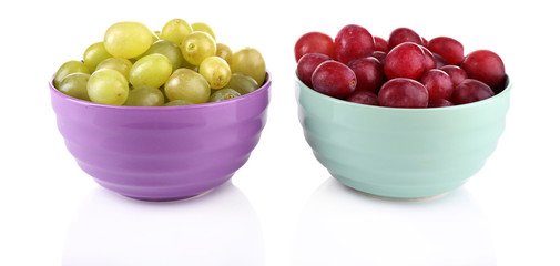 Two bowls of green and red grapes isolated on white