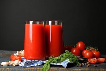 Glasses of tasty tomato juice and fresh tomatoes