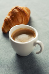 Breakfast concept: cup of coffee and croissant