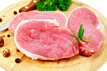 Meat pork slices with rosemary on round board