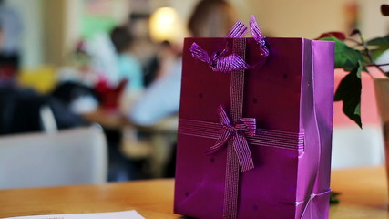 Wrapped gift, present on table in cafe